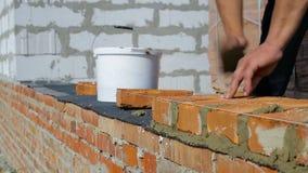 Arbete lägger tegelstenar på en konstruktionsplats på öppen luft stock video