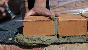Arbete lägger tegelstenar på en konstruktionsplats på öppen luft arkivfilmer