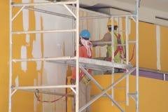 Arbete på höjd, målare i handling på en ställning med full PPE och sele royaltyfri fotografi