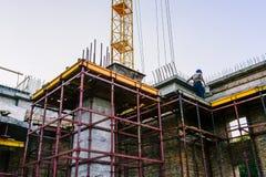 Arbete på konstruktionsplatsen Konstruktion av byggnaden av gul tegelsten Konstruktionsloess och kran Byggande arkivbild