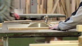 Arbete på produktion med naturligt material Ledar- arbete med trä på maskinen En man i ett grått omslag med ett hjälpmedel lager videofilmer
