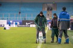 Arbete på stadion drar en linje på fältet Royaltyfria Bilder
