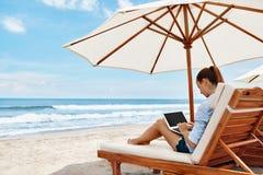 Arbete på stranden Affärskvinna som direktanslutet utomhus arbetar på bärbara datorn Royaltyfri Fotografi