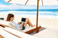 Arbete på stranden Affärskvinna som direktanslutet utomhus arbetar på bärbara datorn arkivfoton