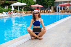 Arbete under ferierna, en kvinna möter jul i ett tropiskt land Ung kvinna i Santa Claus hattarbete på att sitta för bärbar dator royaltyfri bild