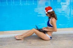 Arbete under ferierna, en kvinna möter jul i ett tropiskt land Ung kvinna i Santa Claus hattarbete på att sitta för bärbar dator royaltyfria foton