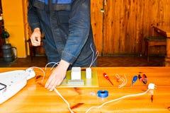 Arbeten för en elektriker för man samlar funktionsdugliga, den elektriska strömkretsen av en stor vit gatalampa med trådar, en re royaltyfri bild