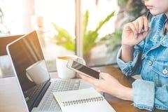 Arbeten för en hand för kvinna` s på en anteckningsbokdator och en mobiltelefon I Royaltyfri Bild