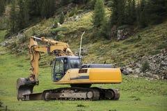 Arbeten för maskineri för grävskopaladdare eller backhoeväntande utomhus på otztal fjällängar Royaltyfria Foton