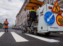 Arbeten på att applicera den nya vägmarkeringen Arkivbild