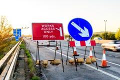 Arbeten tar fram endast tecknet på UK-Motorwayafton Royaltyfri Foto