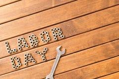 Arbets- dag - inskriften och skiftnyckeln På träbakgrund Royaltyfri Bild