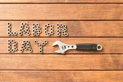 Arbets- dag - inskriften och skiftnyckeln På träbakgrund Royaltyfria Foton