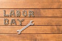 Arbets- dag - inskriften och skiftnyckeln På träbakgrund Arkivbild