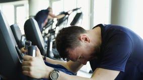 Arbetsam manlig idrottsman nen som rider den stationära cykeln i konditionklubban, motivation lager videofilmer
