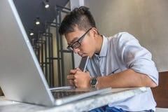 Arbetsam ung man som använder mobiltelefonen och att koncentrera för bärbar dator fotografering för bildbyråer