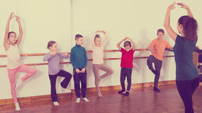 Arbetsamma pojkar och flickor som repeterar balett, dansar i studio Royaltyfri Foto