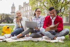 Arbetsamma studenter som känner sig förbluffa dricka kaffe i parkera arkivfoton