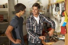Arbetsbänk för faderTeaching Son To bruk i garage arkivfoton