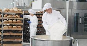 Arbetsdagsi en gammal bagare för bageribransch som förbereder degen, lastade av mjölet i behållarebakgrundsarbetarna lager videofilmer