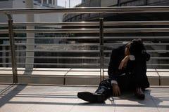 Arbetslöns belastade den unga asiatiska affärsmannen som utomhus sitter på golv Fel- och friställningbegrepp arkivbild