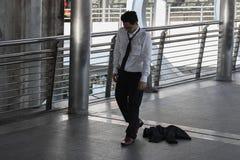 Arbetslöns belastade den unga asiatiska affärsmannen som utomhus sitter på golv Fel- och friställningbegrepp royaltyfria bilder