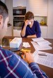 Arbetslös make som granskar räkningarna, och fru fotografering för bildbyråer