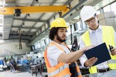 Arbetsledare med den manuella arbetaren som diskuterar över skrivplattan i metallbransch Royaltyfri Foto