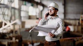 Arbetsledare med den talande telefonen för plan Man i hård hatt och formellt klädanseende på plats med plan, i händer och samtal lager videofilmer