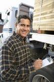 Arbetsledare med skrivplattan med lastbilen som laddas med trä Arkivbilder