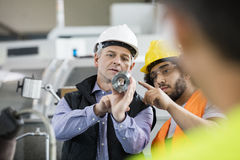 Arbetsledare och manuell arbetare som diskuterar över metall i bransch Arkivbild