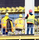Arbetsledare och två arbetare på rekonstruktionområdet royaltyfri foto