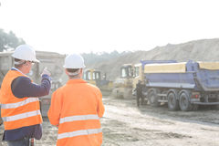 Arbetsledare som förklarar plan till kollegan på konstruktionsplatsen Royaltyfri Fotografi