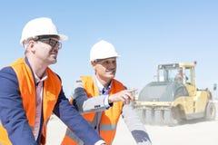 Arbetsledare som förklarar plan till kollegan på konstruktionsplatsen mot klar himmel Royaltyfri Fotografi