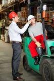 Arbetsledare som instruerar gaffeltruckchauffören Royaltyfri Fotografi