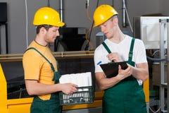 Arbetsledare som kontrollerar kvaliteten av färdigt gods Fotografering för Bildbyråer