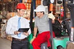Arbetsledare som meddelar med gaffeltruckchauffören Arkivfoto
