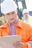 Arbetsledarehandstil på skrivplattan på konstruktionsplatsen med kollegan i bakgrund Arkivfoto