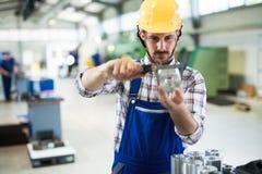 Arbetsledaren som gör kvalitets- kontroll, och pruductionen kontrollerar in fabriken Arkivfoton