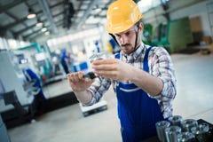Arbetsledaren som gör kvalitets- kontroll, och pruductionen kontrollerar in fabriken Arkivfoto