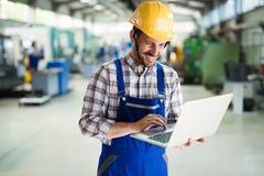 Arbetsledaren som gör kvalitets- kontroll, och pruductionen kontrollerar in fabriken Arkivbild