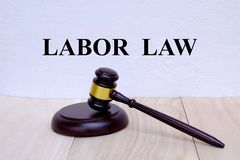 Arbetsmarknadslagstiftning som är skriftlig på väggen med auktionsklubban på träbakgrund lag för begreppet för bakgrund 3d isoler arkivbilder