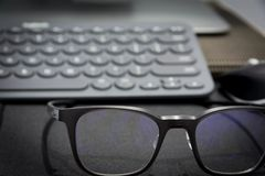 Arbetsområde med tangentbord- och ögonexponeringsglas Arkivbild