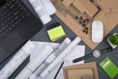 Arbetsplats av arkitekten - anteckningsbok, räknemaskin, byggnadsritningar arkivfoto