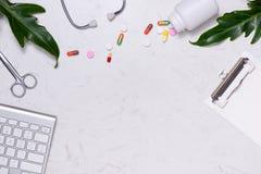 Arbetsplats av en doktor Stetoskop, skrivplatta, preventivpillerar och annat s arkivbild