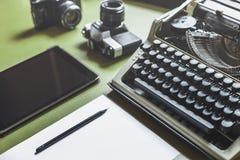 Arbetsplats av en journalist, författare, Blogger Parallell skrivmaskin, Digital minnestavla och filmkamera på den gröna tabellen fotografering för bildbyråer
