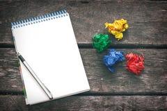 Arbetsplats av konstnären, författare ge sig aldrig upp Notepad med det tomma arket av papper, pennan och mångfärgade skrynkliga  Arkivbild