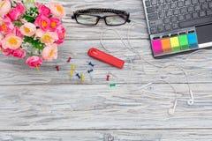 Arbetsplats: bärbar dator, exponeringsglas och blommor Arkivfoton