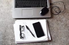 Arbetsplats - bärbar dator, smart telefon, anteckningsbok, penna och exponeringsglas royaltyfria bilder