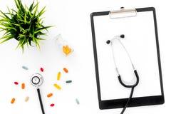Arbetsplats för doktors` s i klinik _ Fästa ihop blocket, stetoskopet och kulöra preventivpillerar på bästa sikt för vit bakgrund royaltyfri bild